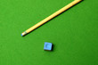 cue stick wit chalk block on green pool table
