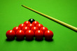 Cue stick and snooker balls over green surface