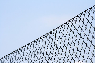 Chainlink fence against blue background