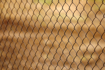 Chainlink fence against brown background - depth of field