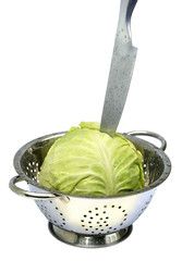 Cabbage in a colander with a knife on white isolated.