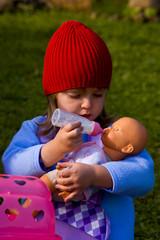 Cute Little girl kissing her favorite doll