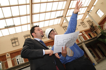 contractor showing blueprints to investor