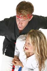 Woman in martial arts uniform elbows a man