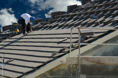 Roofer Laying Tile Shingles on a New Home - 4737417