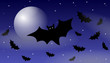 Halloween bats flying under the moon