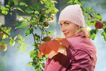 Beautiful girl with autumn leaves near the apple tree and blue f