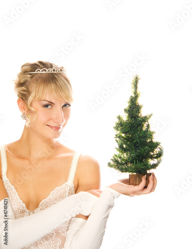 Beautiful blond girl holding a Christmas tree isolated on white