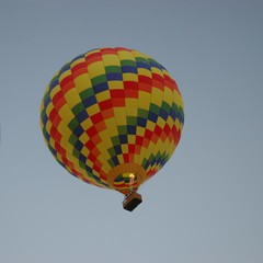 Colorful checkered hot air balloon against light blue sky