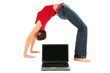 Young woman performing yoga in front of a laptop