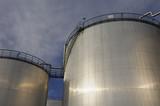 large oil tanks at sundown poster