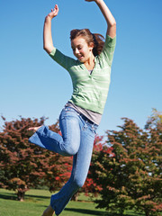 teenage girl jumping in air on autumn day