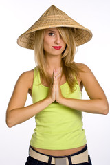 The young woman in a straw hat on a white background. Hands toge