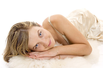 Beautiful woman with blue eyes laying on white fur