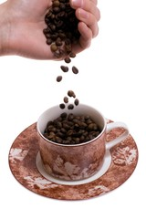 Woman's hand dropping coffee beans into cup