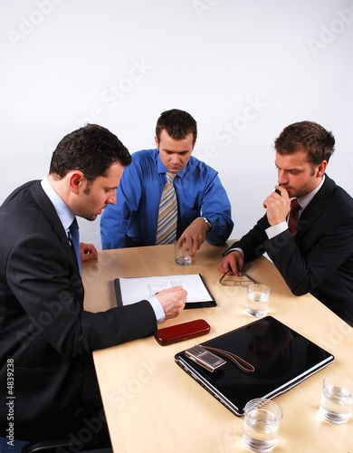 Three businessmen handling negotiations.