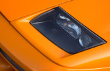 Headlamp on a vivid orange Italian super car poster