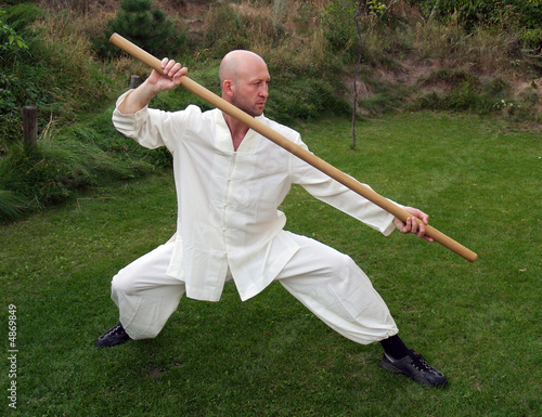The man doing Tai Chi with a pole