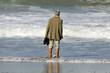 femme âgée les pieds dans l'eau sur la plage