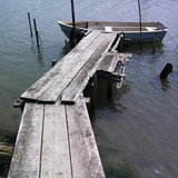 Boat at wood plank jetty poster