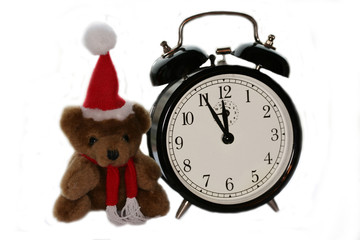 teddy bear in christmas red cap and old alarm clock