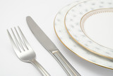 Table setting with plates knife and fork on white background poster
