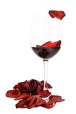 Glass on red wine with a rose and rose petals isolated on white