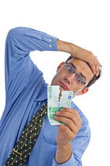 Depressed businessman holding ripped money in front of face