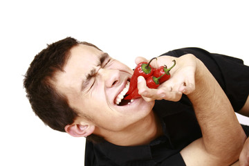 young man eating an red chili