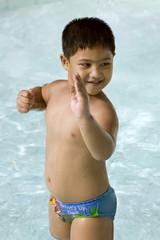 kid doing karate move in the swimming pool