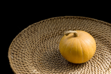 Yellow pumpkin on wickerwork plate-2