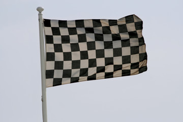 checkered race flag flapping in the sky