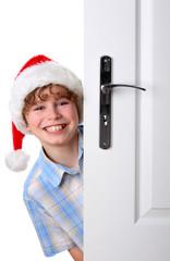 Boy with Santa's Hat peeking behind the door