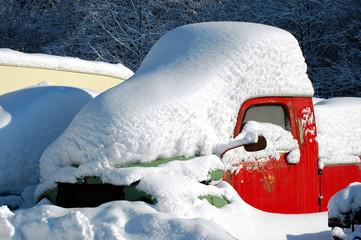 rotes Auto eingeschneit im Winter