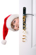 Boy with Santa's Hat peeking behind the door