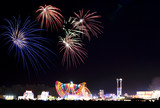 Fireworks bursting over a funfair – long exposure poster