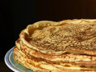 Mehrere Pfannkuchen auf einem Teller, Hintergrund schwarz