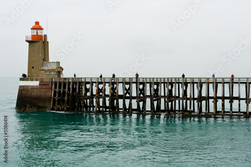 Fishermen on a high wooden pier near a beacon light