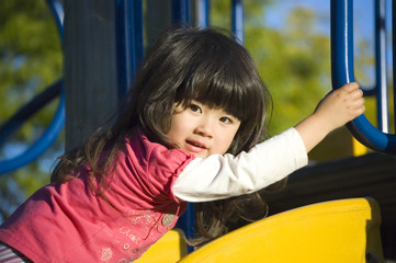 Cute little girl climbing up the slide at playground
