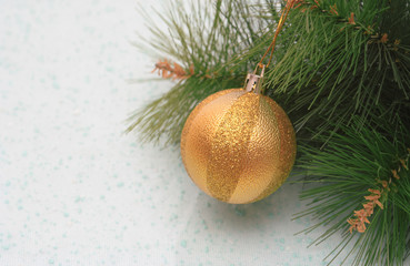 New Year's gold sphere on a pine branch