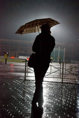 lonely figure on the light athletic stadium under the rain