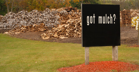 "Sign in front of large wood piles saying ""Got Mulch?"""