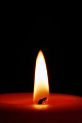 Red candel burning in the dark