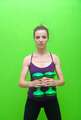 Pretty girl with dumbbells and green backgound