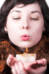 Girl in red coat blow on candle