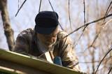 senior framing a roof of an hunter shack poster