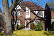 tudor style home with leaf covere lawn