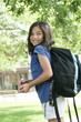 Eight year old girl with backpack excited about school