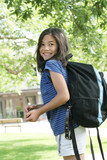 Eight year old girl with backpack excited about school poster