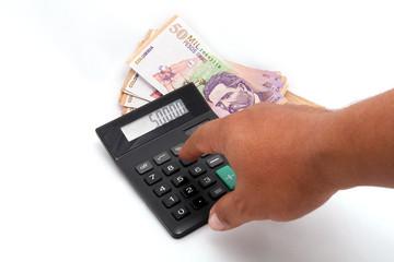 Mano, billetes y calculadora